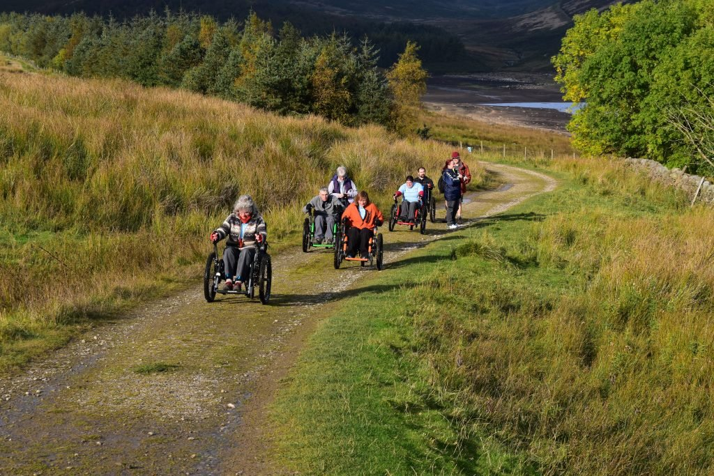 A group of people using Mountain Trike All-Terrain Wheelchairs at Yorkshire Water's Grimwith Reservoir.